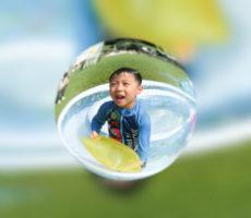 <strong>作品No:76 水滴になっちゃった</strong><br><br>プールで遊んでいるところを魚眼レンズで撮影したら、水滴に入ったみたいになりました。